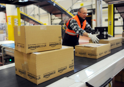 A file photo dated 20 December 2010 showing an employee of the online-retailer Amazon putting packages onto a conveyor band at the logistics centre in Bad Hersfeld, Germany.  EPA