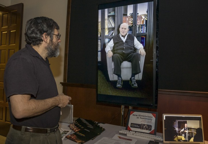 """In this photo taken Tuesday, Jan. 29, 2013, University of Southern California Institute for Creative Technologies, computer scientist David Traum, left, interacts with Holocaust survivor, Pinchas Gutter, seen on a """"Virtual Survivor Visualization,"""" at the USC campus in Los Angeles. A collaboration with the Shoah Foundation is digitizing aging Holocaust survivors to create three-dimensional holograms that would not only be able to tell their stories to future generations but to engage in dialogue with them. (AP Photo/Damian Dovarganes)"""