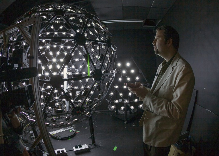 """In this photo taken Tuesday, Jan. 29, 2013, University of Southern California Institute for Creative Technologies, associate director for graphics research, Paul Debevec, explains the Lighting Stage X, a LED-filled sphere used to help create realistic virtual characters at the Graphics Lab in Playa Vista area of Los Angeles. The """"Virtual Survivor Visualization,"""" a collaboration with the Shoah Foundation used the Lighting Stage X to digitize aging Holocaust survivors to create three-dimensional holograms that would not only be able to tell their stories to future generations but to engage in dialogue with them. (AP Photo/Damian Dovarganes)"""