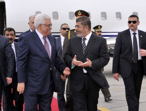 Palestinian President Mahmoud Abbas, second left, walks with Egyptian President Mohammed Morsi, center, following Abbas' arrival in Cairo, Egypt, for the Organization of Islamic Cooperation summit, Tuesday, Feb. 5, 2013. (AP Photo/Egyptian Presidency)