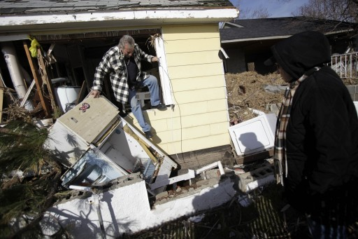 In a Tuesday, Nov. 20, 2012 file photo, Joe Vanvaketis climbs out of his home, which was severely damaged by Superstorm Sandy, after trying to recover some personal items while his wife Inez Vanvaketis watches in the Oakwood Beach section of Staten Island, New York. (AP Photo/Seth Wenig, File)