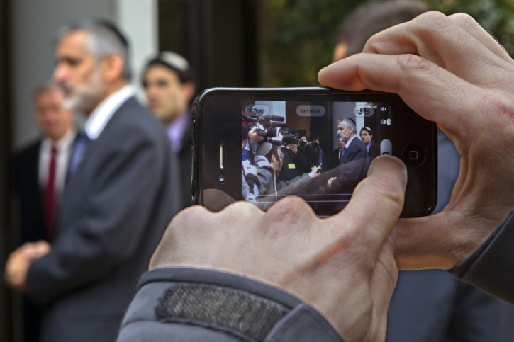 Eli Yishai, one of the leaders of the ultra-Orthodox Shas party, seen on a cell phone as his picture is taken in Jerusalem residence. EPA/JIM HOLLANDER