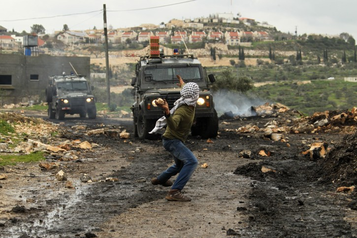 Palestinian protesters hurl stones at Israeli soldiers in West Bank, 1 February 2013. EPA/ALAA BADARNEH