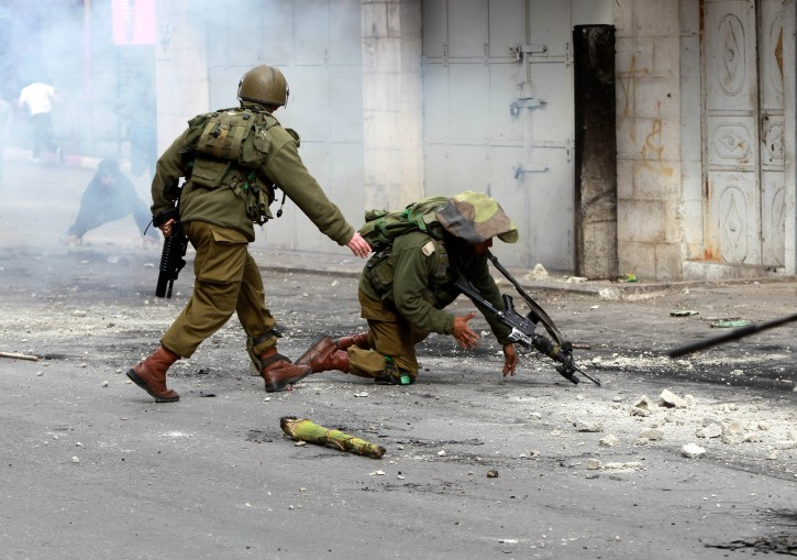 An Israeli Border Policeman falls to the ground after being hit by a missile during clashes with Palestinians protesting in the West Bank city of Hebron, 24 February 2013. EPA/ABED AL HASHLAMOUN