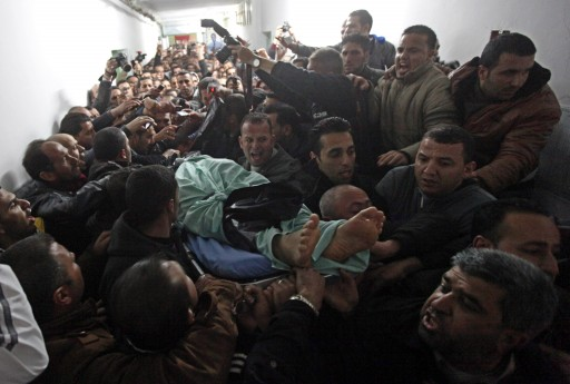 Palestinian mourners carry the body of Arafat Jaradat, who died in an Israeli prison, to his funeral in Hebron, 24 February 2013. EPA/ABED AL HASHLAMOUN