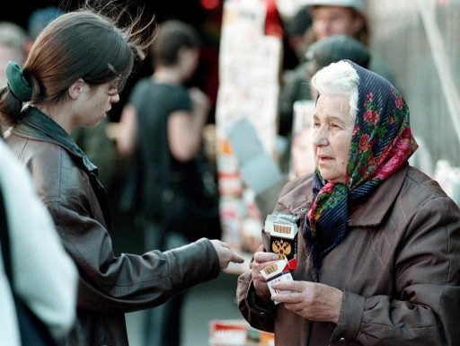 A girl checks out the price for one cigarette by an elderly woman, who sells the cigarettes by the piece on a street market in St. Petersburg, Thursday 24 September. EPA PHOTO/ANATOLY MALTSEV/vk-cl RUSSIA OUT