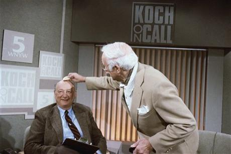 In this March 15, 1987 file photo, New York Mayor Ed Koch gets his head powered by a make-up artist before the start of his new television call-in program,