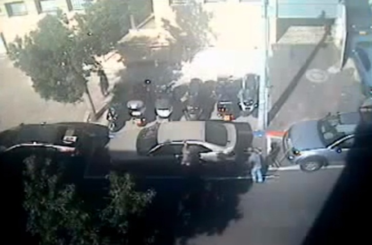 A YouTube video shows workers in Tel Aviv painting a handicapped parking spot around Ben Baruch's legally parked car.
