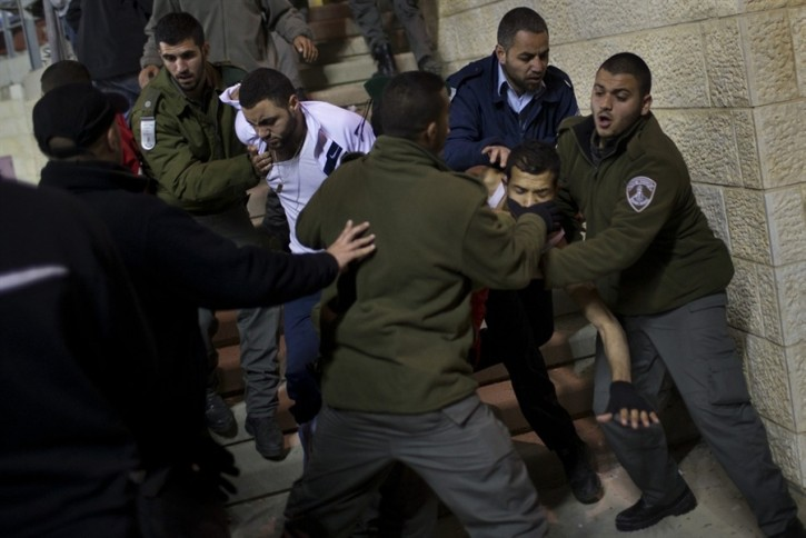 Israeli security forces detain Bnei Sakhnin supporters during a game against Beitar Jerusalem F.C. at the Teddy Stadium in Jerusalem, Sunday, Feb. 10, 2013. (AP Photo/Bernat Armangue)