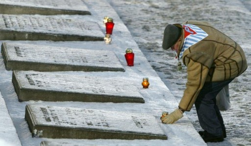 FILE - A survivor places a candle near the Monument for the victims of Fascism during a ceremony in Birkenau January 27, 2005.  Reuters