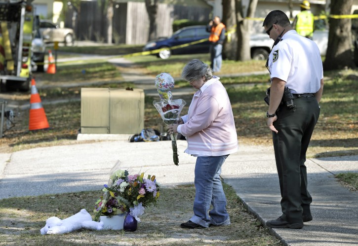 Brenda Bush is escorted by a Hillsborough County Sheriff's deputy as she places flowers, Saturday, March 2, 2013,  at a makeshift memorial in front of a home where a sinkhole opened up underneath a bedroom late Thursday evening and swallowed her son Jeffrey in Seffner, Fla.  Jeffrey Bush, 37, was in his bedroom Thursday night when the earth opened and took him and everything else in his room. Five other people were in the house but managed to escape unharmed. Bush's brother jumped into the hole to try to help, but he had to be rescued himself by a sheriff's deputy. (AP Photo/Chris O'Meara)