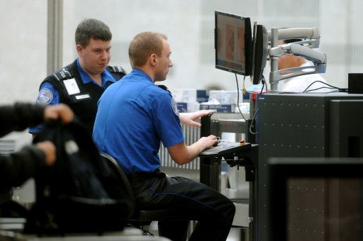 TSA (Transportation Security Administration) officials operate an x-ray machine at a security checkpoint at Washington Dulles International Airport, in Sterling, Virginia. EPA/MICHAEL REYNOLDS