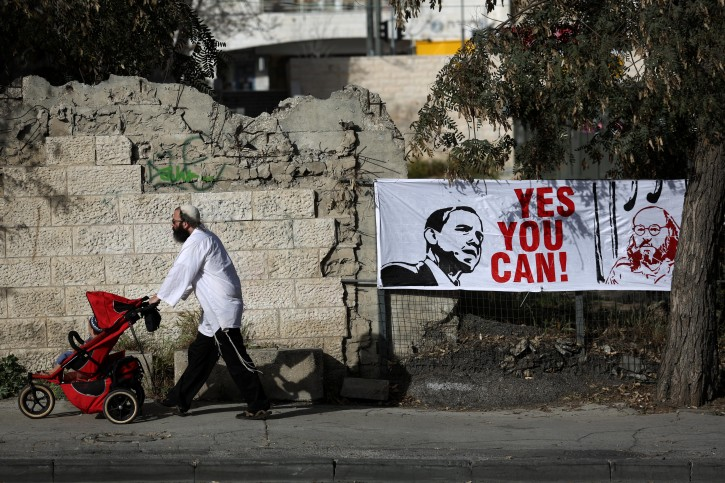Religious Jewish man walk next to a sign with a drawing of U.S. President Barack Obama(L) and Jonathan Pollard (R), a Jewish American who was jailed for life in 1987 on charges of spying on the United States. in Jerusalem, 13 March 2013. EPA/Abir Sultan