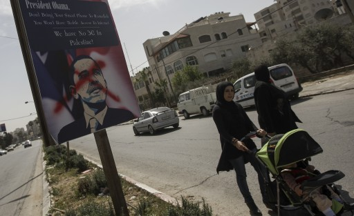 Palestinian women pass placards of US President Barack Obama, along the main road between Jerusalem and Ramallah, in the West Bank town of Ramallah, 14 March 2013. Unknown protesters put X on Obama's placards. in protest of Obama visit to Palestine. EPA/ATEF SAFADI