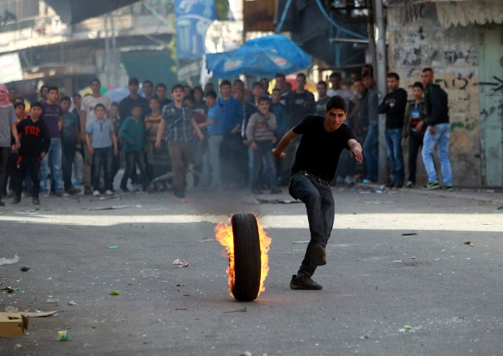 A Palestinian runs next to a burning car tire during clashes with Israeli riot police in Hebron, the West Bank, 14 March 2013. EPA/ABED AL HASHLAMOUN