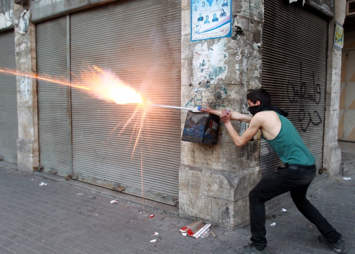 A Palestinian protester launches a firework from a steet corner, aimed at Israeli border police, during clashes with Israeli police in Hebron, the West Bank, 21 March 2013. EPA/ABED AL HASHLAMOUN