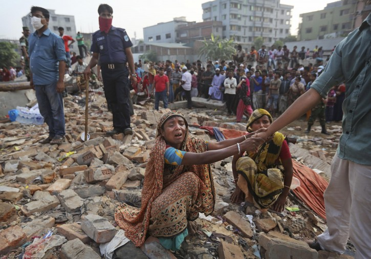 A Bangladeshi woman weeps as she waits at the site of a building that collapsed Wednesday in Savar, near Dhaka, Bangladesh, Friday, April 26, 2013. By Friday, the death toll reached at least 270 people as rescuers continued to search for injured and missing, after a huge section of an eight-story building that housed several garment factories splintered into a pile of concrete.(AP Photo/Kevin Frayer)