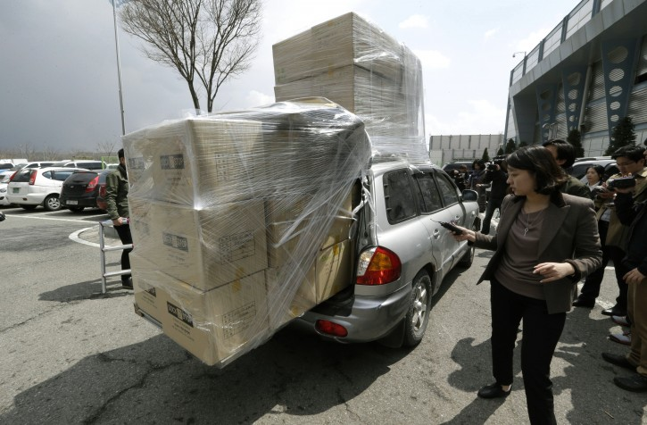 A South Korean vehicle with products from North Korea's Kaesong is surrounded by media upon its arrival at the customs, immigration and quarantine office near the border village of Panmunjom, that has separated the two Koreas since the Korean War, in Paju, north of Seoul, South Korea, Tuesday, April 9, 2013. North Korean workers didn't show up for work at a jointly run factory complex with South Korea on Tuesday, a day after Pyongyang suspended operations at the last remaining major economic link between rivals locked in an increasingly hostile relationship. (AP Photo/Lee Jin-man)