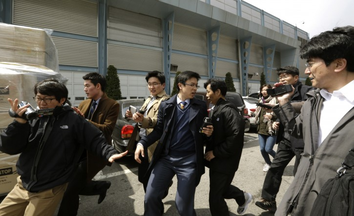 A South Korean worker, fifth from left, who arrives with boxes of products, left seen, from North Korea's Kaesong is questioned by media upon his arrival at the customs, immigration and quarantine office near the border village of Panmunjom, that has separated the two Koreas since the Korean War, in Paju, north of Seoul, South Korea, Tuesday, April 9, 2013. North Korean workers didn't show up for work at a jointly run factory complex with South Korea on Tuesday, a day after Pyongyang suspended operations at the last remaining major economic link between rivals locked in an increasingly hostile relationship. (AP Photo/Lee Jin-man)