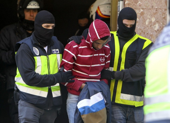 Police agents arrest Algerian Nou Mediouni at his flat in Zaragoza, Spain, 23 April 2013. Spanish judge Santiago Pedraz ordered Mediouni's detention including an accomplice, Moroccan Hassan El Jaaouan living in Murcia, both accused of Islamic terrorism after an investigation proved they were both radicalizing and visited radical and jihad Websites.  EPA/JAVIER CEBOLLADA