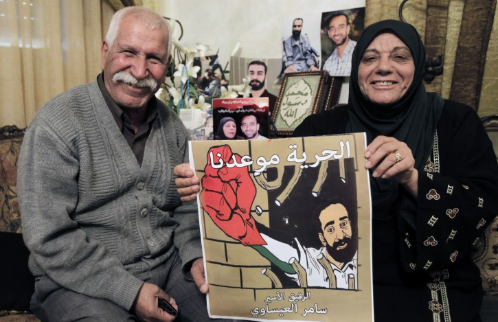The parents of Palestinian hunger striking prisoner Samer Issawi at their home in the Issawiya neighborhood in Arab East Jerusalem, 23 April 2013, as they rejoice that their son has decided to end his hunger strike, which has lasted more than eight months. Samer, 32, has agreed to a deal to serve eight months for allegedly violating bail conditions and will then be freed to his home in Jerusalem. His hunger strike and deteriorating health conditions have sparked protests and concern that he might die while in Israeli custody, even though he is currently in an Israeli hospital and is kept alive with vitamins and liquids drips.  EPA/MAHFOUZ ABU TURK