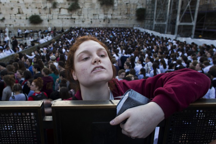 "A Jewish orthodox women follows a prayer organized by the ""Women of the Wall"" organization, not pictured, at the Western Wall, the holiest site where Jews can pray in Jerusalem's old city, Friday, May 10, 2013. (AP Photo/Bernat Armangue)"