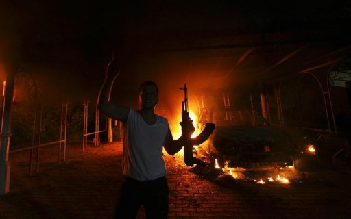 FILE - A protester reacts as the U.S. Consulate in Benghazi is seen in flames during a protest by an armed group September 11, 2012.