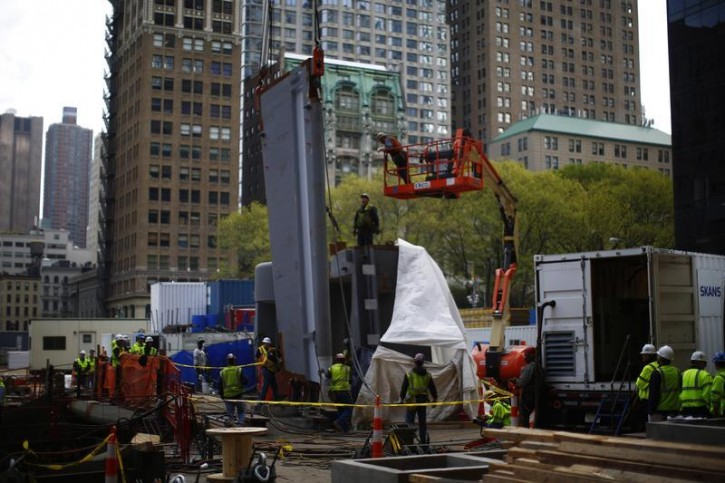Workers lift the first above ground piece of steel into place at the World Trade Center transportation hub in New York May 6, 2013. Not due to open until 2015, the 800,000-square-foot (74,322-square-meter) transit hub will eventually link numerous New York City subway lines with commuter trains and ferry services to neighboring New Jersey. REUTERS/Eric Thayer