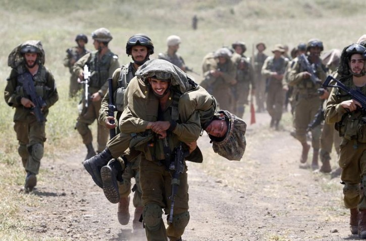 An Israeli soldier carries another soldier as they walk with their comrades during training close to the ceasefire line between Israel and Syria on the Israeli occupied Golan Heights May 7, 2013.  REUTERS/Baz Ratner