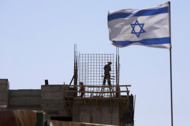 An Israeli flag is seen as labourers work on a construction site in a Jewish settlement near Jerusalem known to Israelis as Har Homa and to Palestinians as Jabal Abu Ghneim May 7, 2013. Prime Minister Benjamin Netanyahu has quietly curbed new building projects in Jewish settlements, an Israeli watchdog group and media reports said on Tuesday, in an apparent bid to help U.S. efforts to revive peace talks with the Palestinians. REUTERS/Ronen Zvulun
