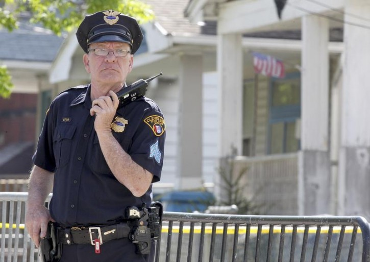 A Cleveland police officer stands guard outside the house where three women who vanished as teenagers about a decade ago were discovered alive, in Cleveland, Ohio May 7, 2013. Authorities were alerted to their whereabouts on Monday evening by a frantic emergency call from one of them moments after she was freed from the house by a neighbor who said he heard screaming and came to her aid. The home's owner and his two brothers were arrested, police said on Tuesday. REUTERS/Aaron Josefczyk