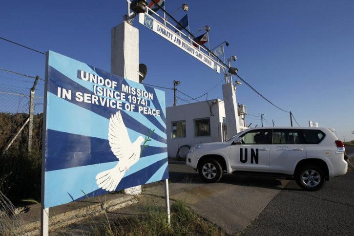 A United Nations armoured car drives through a gate at a U.N. base near the Kuneitra border crossing between Israel and Syria, in the Israeli-occupied Golan Heights May 7, 2013. Reuters