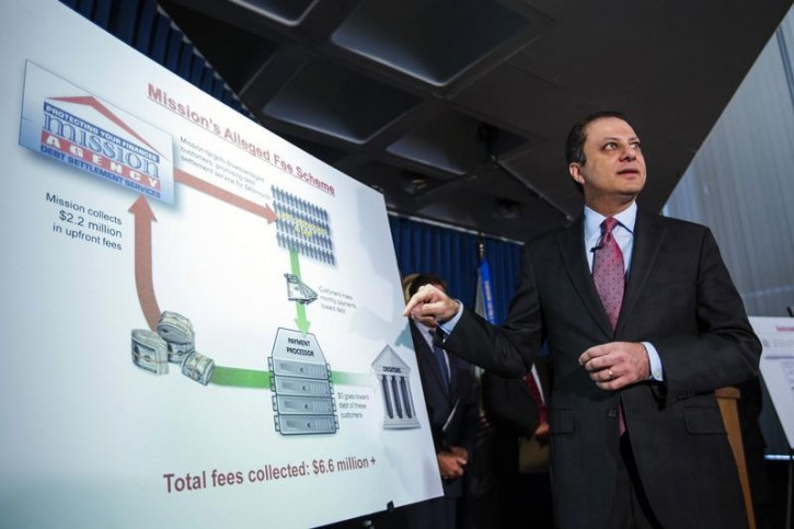 Preet Bharara, U.S. Attorney for the Southern District of New York points at a chart describing charges being brought against the debt settlement company Mission Settlement Agency, at a news conference in New York, May 7, 2013. REUTERS/Lucas Jackson