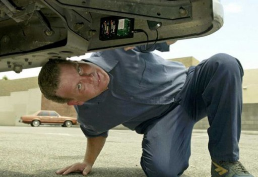 John LaSage demonstrates how to set a surveillance vehicle tracker underneath his truck's bumper.</p>  <p>Photo by AP Photo