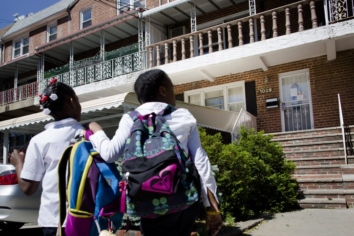 School children pass the home of a 10-year-old Brooklyn boy who police say on Monday picked up a gun dropped by a would-be robber dressed as a delivery man and fired a shot, Tuesday, June 4, 2013, in New York. No injuries were reported. (AP Photo/John Minchillo)