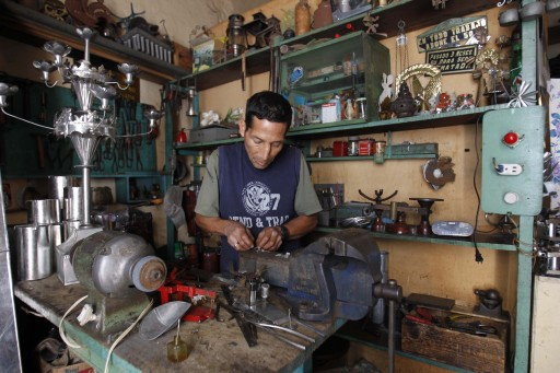 A tinsmith works at his workshop in downtown Quito, Ecuador, Wednesday, June 26, 2013. With Edward Snowden stuck in Moscow and Washington pushing hard for his return, many Ecuadoreans began realizing that this small country's deep economic ties with the U.S. could make it the one with the most to lose in the high-stakes international showdown over the National Security Agency leaker, as nearly half of Ecuador's foreign trade depends on the U.S. (AP Photo/Dolores Ochoa)
