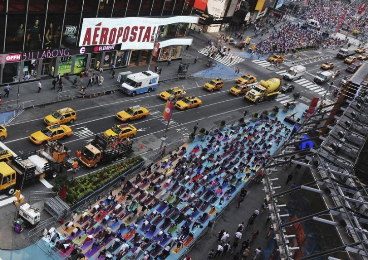 "People practice yoga on the morning of the summer solstice in New York's Times Square June 20, 2012. The ""Solstice in Times Square"" event on Wednesday brought out thousands of participants to celebrate the year's longest day in New York.  REUTERS/Shannon Stapleton"