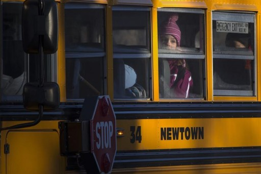 FILE - A student from Sandy Hook Elementary School stares out of the window of a bus that is making its way to their new school in Monroe, as they leave Newtown, Connecticut, January 3, 2013.  Reuters