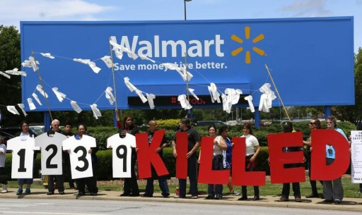 FILE - Protesters hold up a sign commemorating those killed in recent clothing factory tragedies in Bangladesh outside Wal-Mart Stores Inc. headquarters in Bentonville, Arkansas June 5, 2013. The annual shareholders meeting for Walmart takes place June 7, 2013.  REUTERS/Rick Wilking
