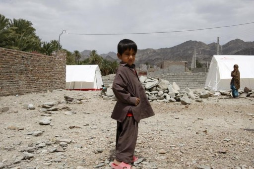 FILE - A boy stands in front of tents after an earthquake in Gosht, about 1,316 km (817 miles) southeast of Tehran, in this April 18, 2013 photo taken during government tour to affected areas.  Reuters