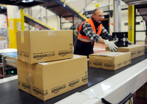 FILE -  A file photo dated 20 December 2010 showing an employee of the online-retailer Amazon putting packages onto a conveyor band. EPA