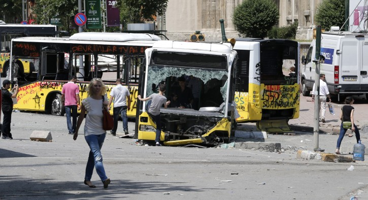 People walk near by damaged public buses in Istanbul, Turkey 04 June 2013. More than 2,300 people have been injured and one person killed during four days of fierce clashes between protesters and police in Turkey, according to a doctors' association, as the prime minister blamed 'extremist elements' for the riots. More than 1,480 people have been wounded in clashes in Istanbul, the country's largest city, with some 800 more injured in the capital Ankara and the Aegean city of Izmir.  EPA/TOLGA BOZOGLU