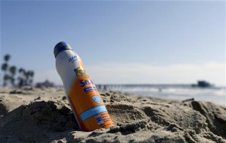 A bottle of Banana Boat sunscreen is shown in the sand.<br /> (AP Photo/Chris Carlson)