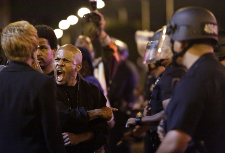 A protester (2nd L) shouts as Los Angeles Police try to remove protesters from the intersection of Exposition and Crenshaw boulevards, following the George Zimmerman verdict in Los Angeles, California, July 13, 2013. REUTERS/Jason Redmond