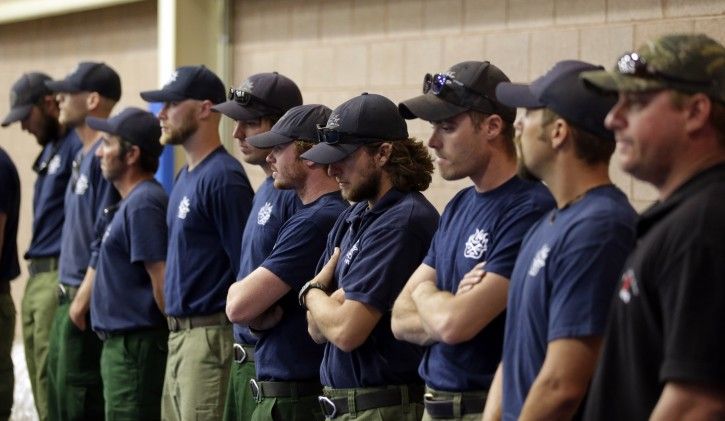 Firefighters wait to go inside for a memorial service in Prescott, Ariz., Monday, July 1, 2013. The firefighters were honoring 19 Granite Mountain Hotshot firefighters who were killed while battling an out-of-control wildfire near Yarnell, Ariz., on Sunday. (AP Photo/Chris Carlson)