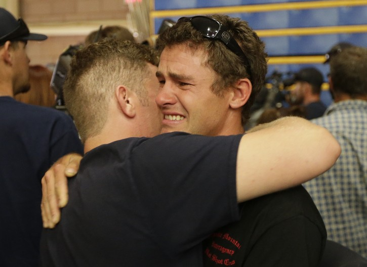 Firefighters embrace as a group during a memorial service Monday, July 1, 2013, in Prescott, Ariz., honoring their 19 fellow firefighters killed battling a wildfire near Yarnell, Ariz., Sunday. The elite crew of firefighters were overtaken by the out-of-control blaze as they tried to protect themselves from the flames under fire-resistant shields. (AP Photo/Chris Carlson)