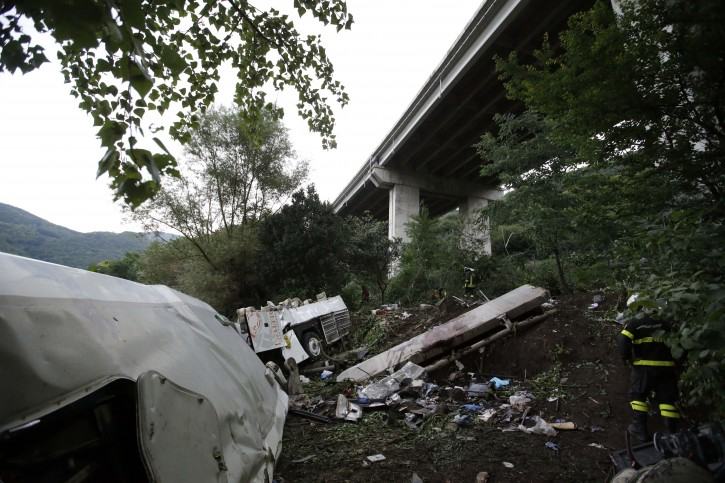 A firefighter stands near the wreckage of a bus following a crash near Avellino, southern Italy, Monday, July 29, 2013. A tour bus filled with Italians returning home after an excursion plunged off a highway into a ravine in southern Italy on Sunday night after it had smashed into several cars that were slowed by heavy traffic, killing at least 38 people, said police and rescuers. Flashing signs near Avellino, outside Naples, had warned of slowed traffic ahead along a stretch of the A16 autostrada, a major highway crossing southern Italy, before the crash occurred, said highway police and officials, speaking on state radio early Monday. They said the bus driver, for reasons not yet determined, appeared to have lost control of his vehicle. (AP Photo/Gregorio Borgia)