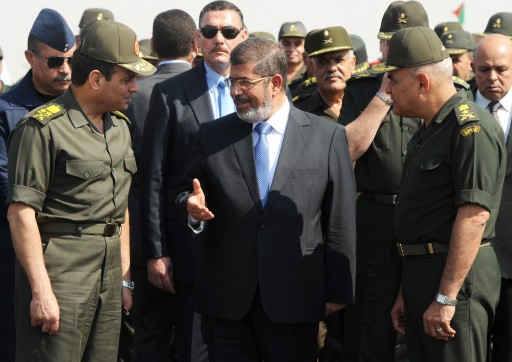 FILE - In this Wednesday, Oct. 10, 2012 file image released by the Egyptian Presidency, Egyptian President Mohammed Morsi, center, speaks with Minister of Defense, Lt. Gen. Abdel-Fattah el-Sissi, left, at a military base in Ismailia, Egypt.  AP