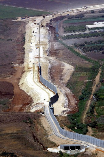 This Tuesday, July 29, 2003 file photo is an aerial view showing workers constructing part of the fence Israel is building to separate Israeli controlled areas, left, from Palestinian areas, right, in the northern West Bank. (AP Photo/Lefteris Pitarakis, File)
