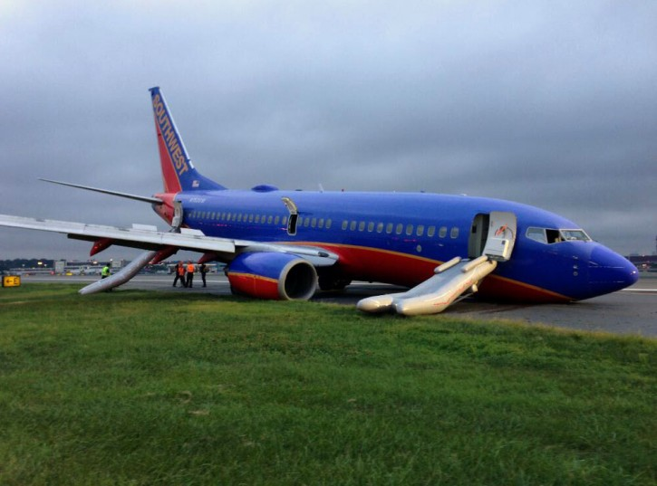 NTSB agents investigate an accident involving nose-gear collapse of a southwest airlines plane, Monday, July 22, 2013, in New York. (AP Photo/NTSB)